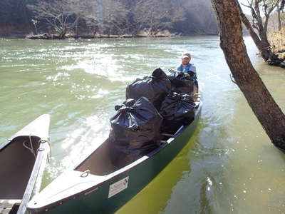 VISTA in canoe with bags of trash